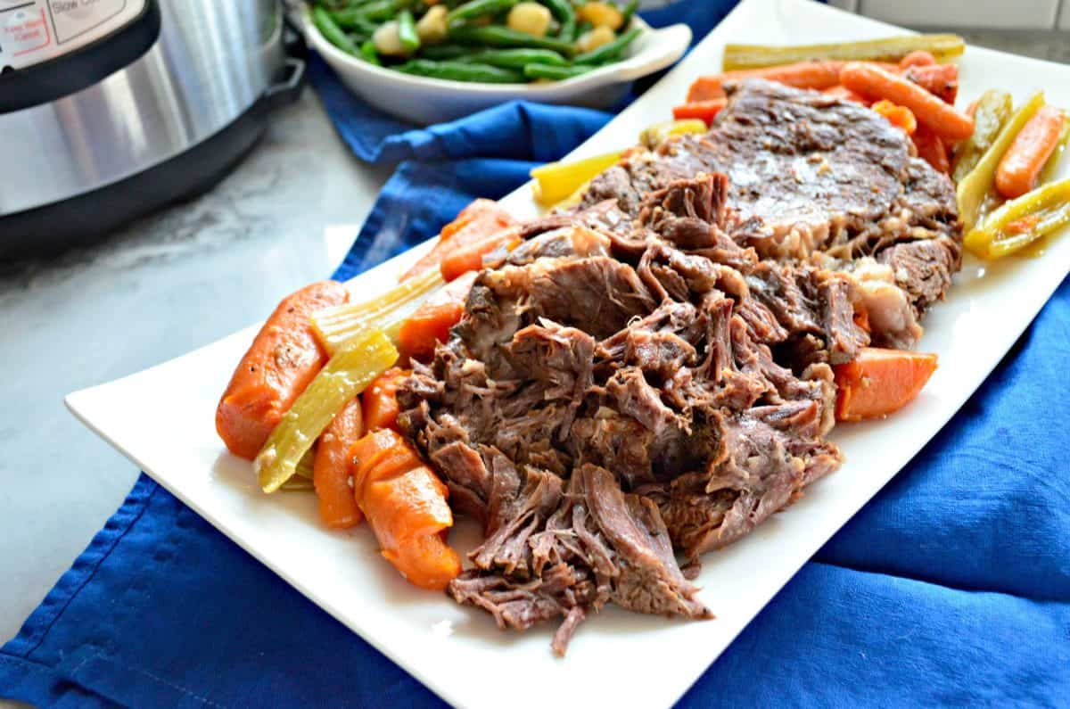 top view of rectangular platter of pot roast with cooked carrots and celery on blue tablecloth.