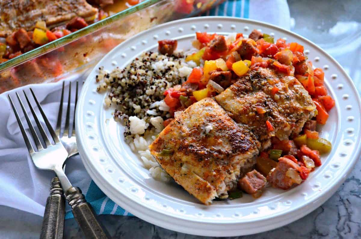 plated baked mahi mahi with chopped veggies and sausage on bed of rice and quinoa with forks.