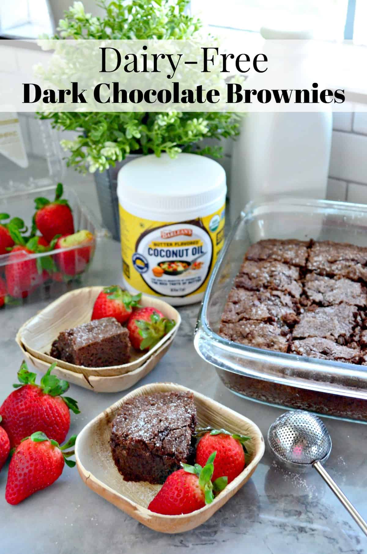 2 square bowls with slice of chocolate brownie and fresh strawberries in front of brownie pan.