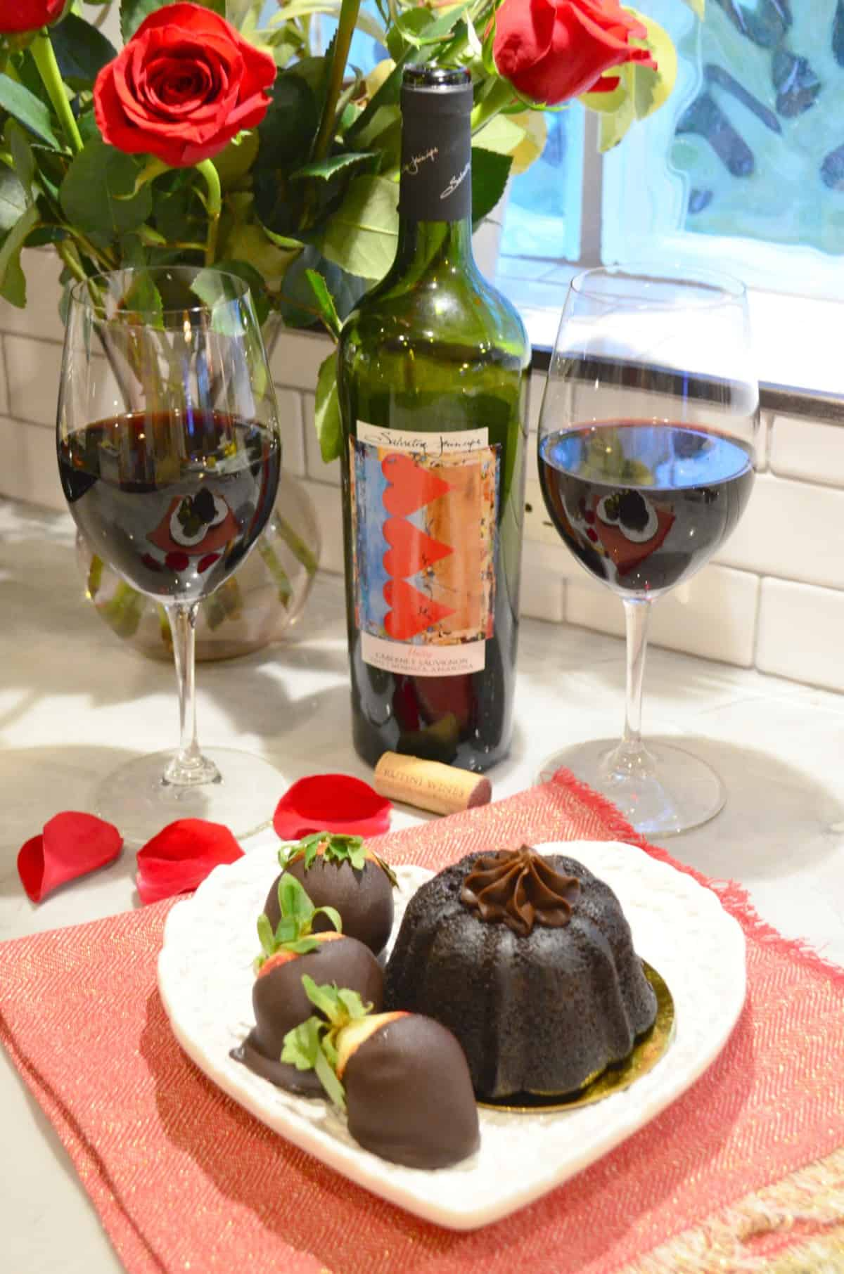 two glasses of wine  and bottle behind plated chocolate cake plated with chocolate dipped strawberries.