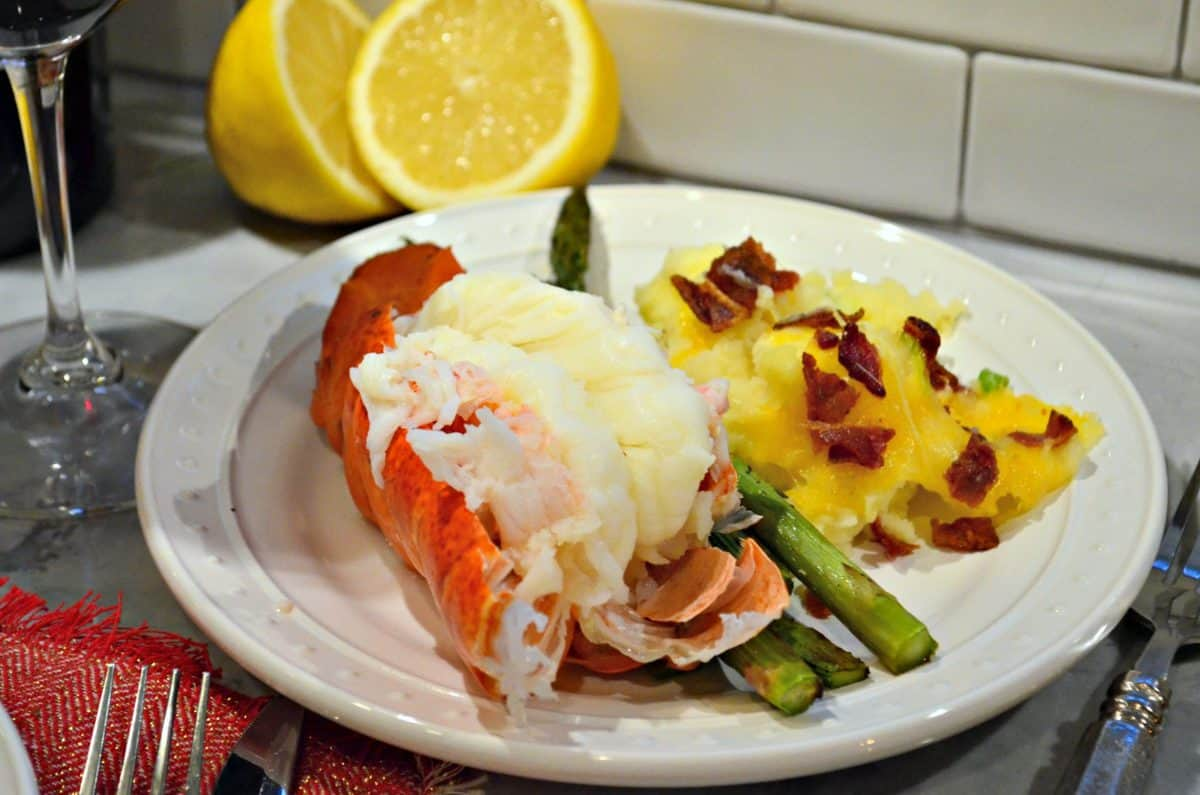 plated cooked lobster tail with potatoes and asparagus with cut fresh lemon in background.