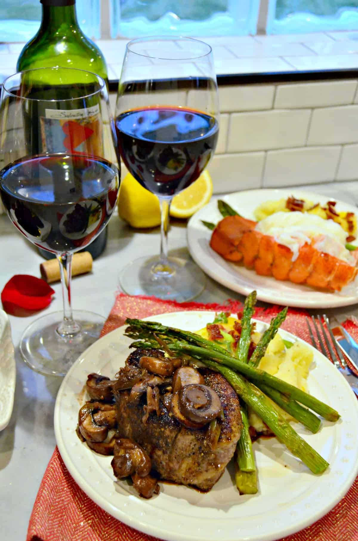 two glasses of wine next to plated chocolate cake, steak, and lobster with asparagus and potatoes.