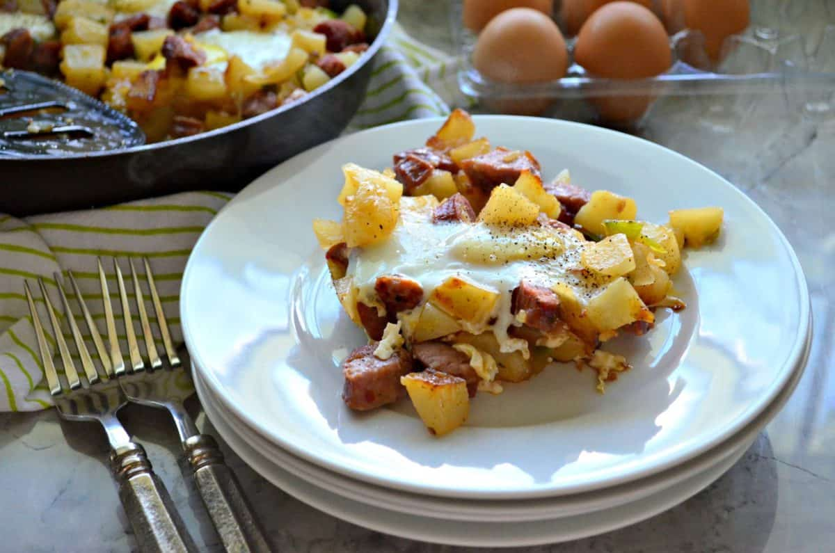 plated diced potatoes, sausage, over easy eggs, peppers on plate next to forks with egg carton in background.