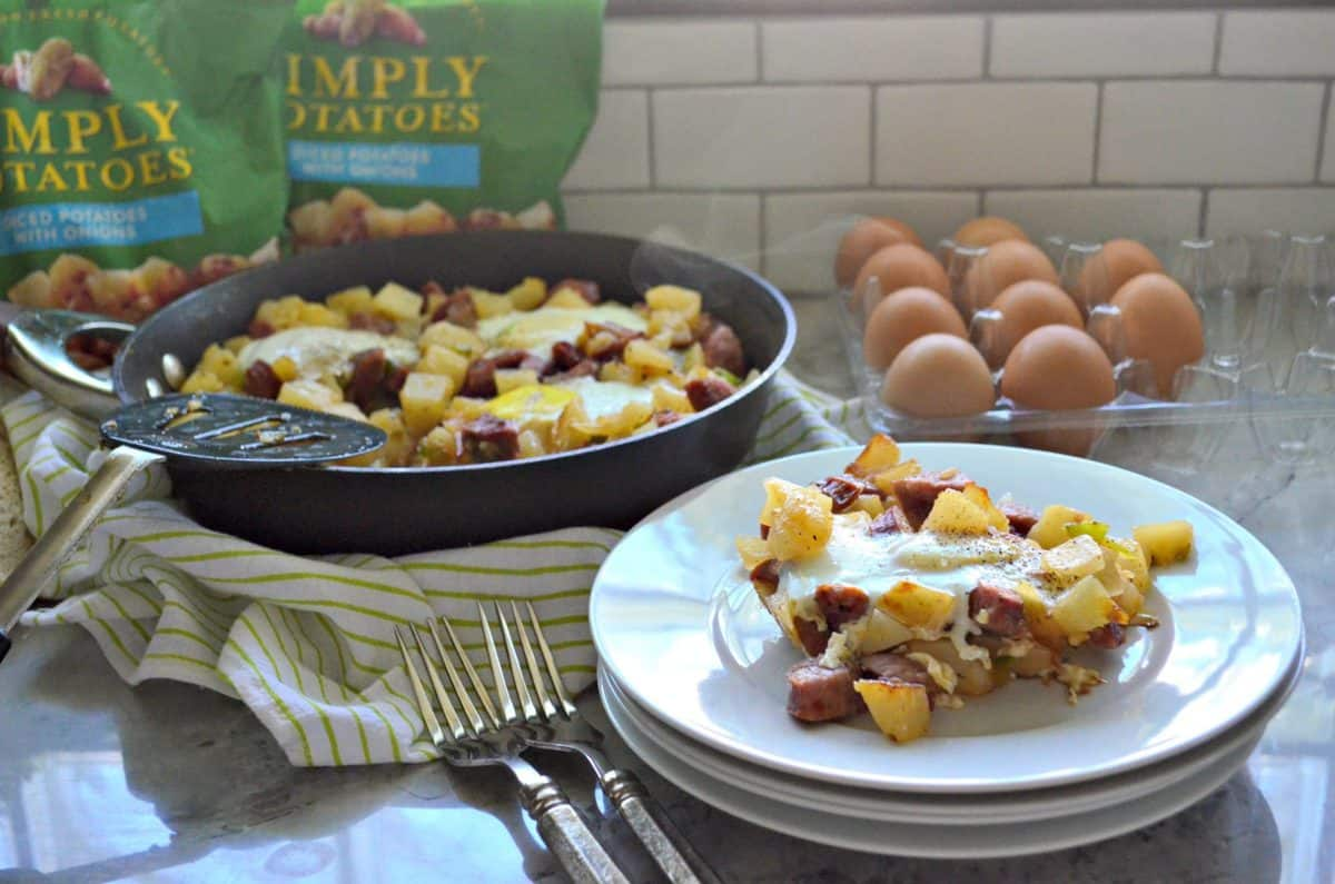 plated diced potatoes, sausage, over easy eggs, peppers, and pepper in front of skillet next to forks.