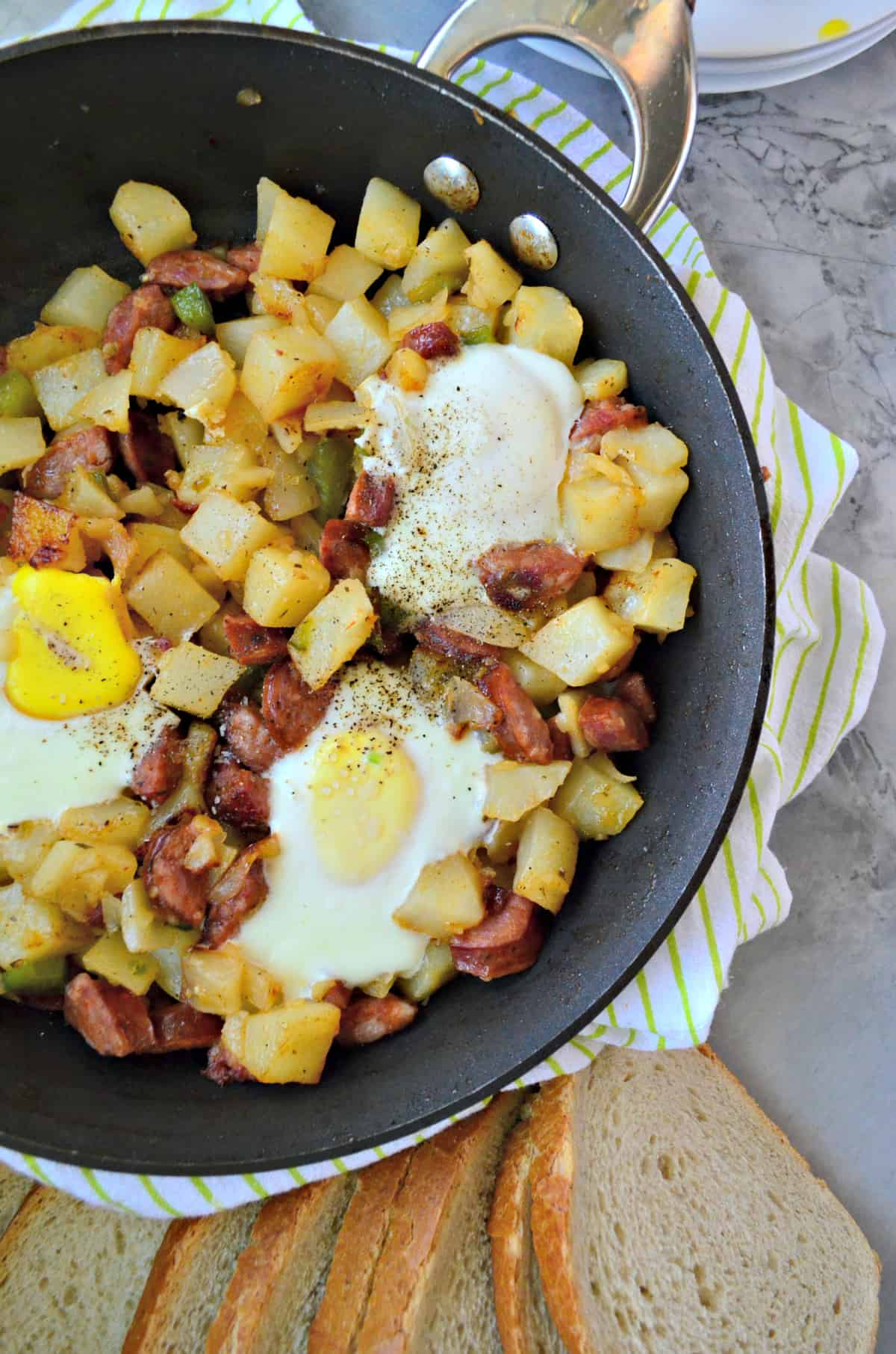 closeup of diced potatoes, sausage, over easy eggs, peppers, and pepper in skillet on counter.