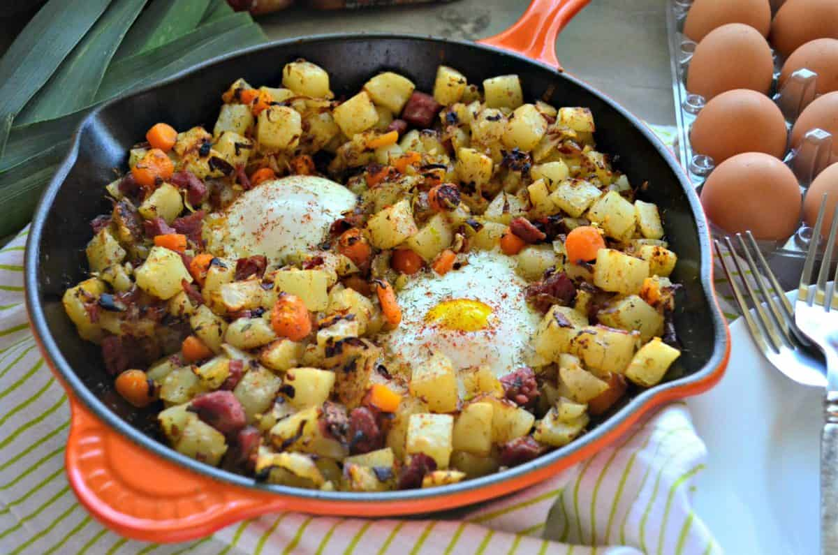 Corned Beef Hash in skillet with overeasy eggs next to egg carton and fresh leek.