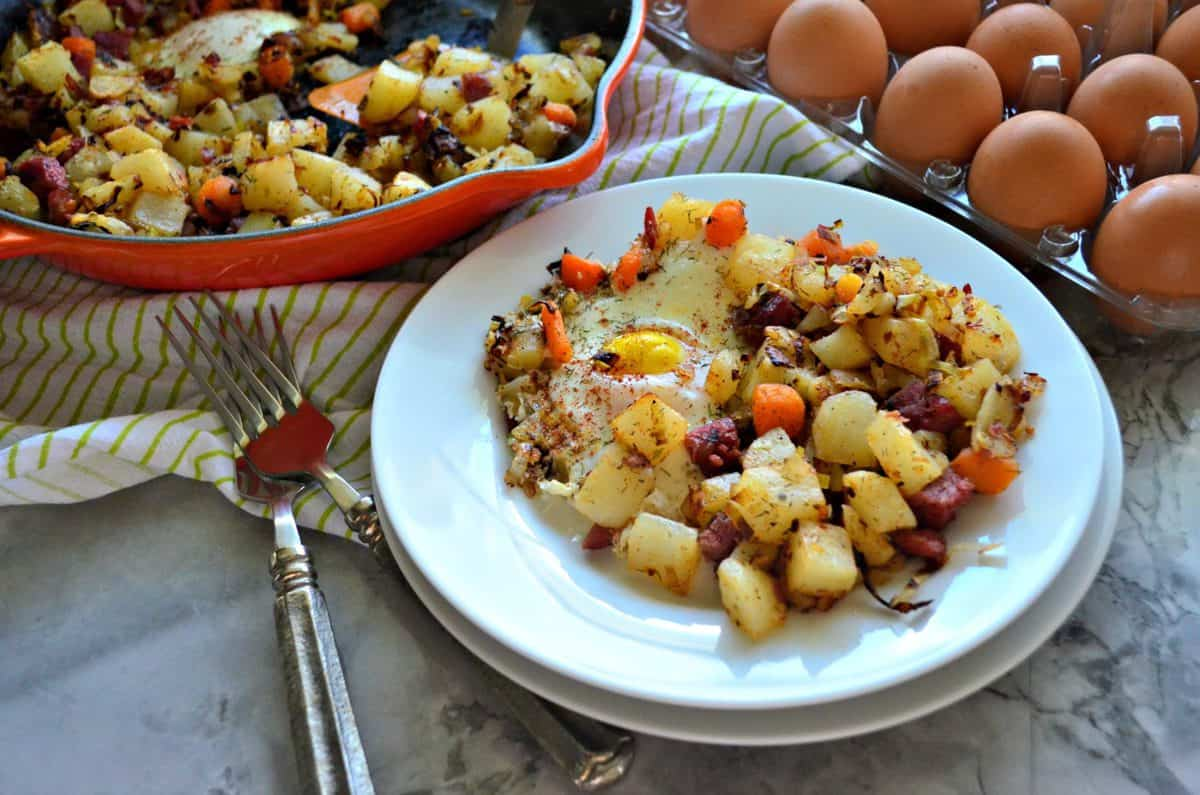 plated Corned Beef Hash with over easy eggs in front of egg carton and skillet.