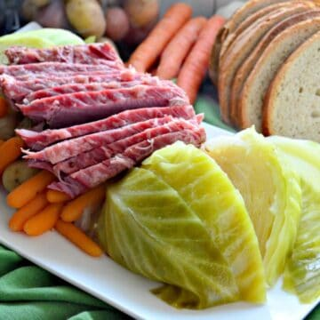 Instant Pot Corned Beef & Cabbage on a platter with rye bread on the side