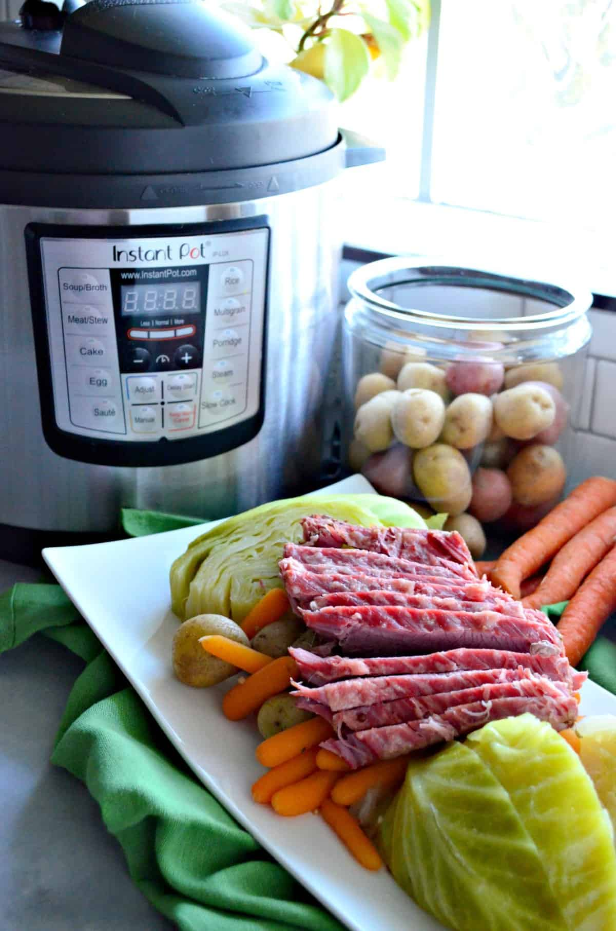 Instant Pot Corned Beef & Cabbage plated with Instant Pot in the background.