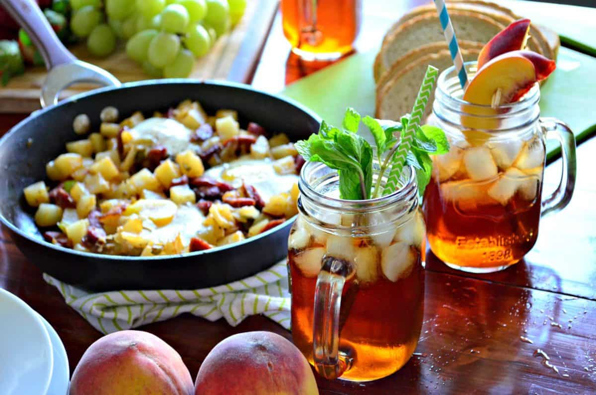 Mint Iced Tea and peach iced tea next to fresh peaches and breakfast skillet on countertop.