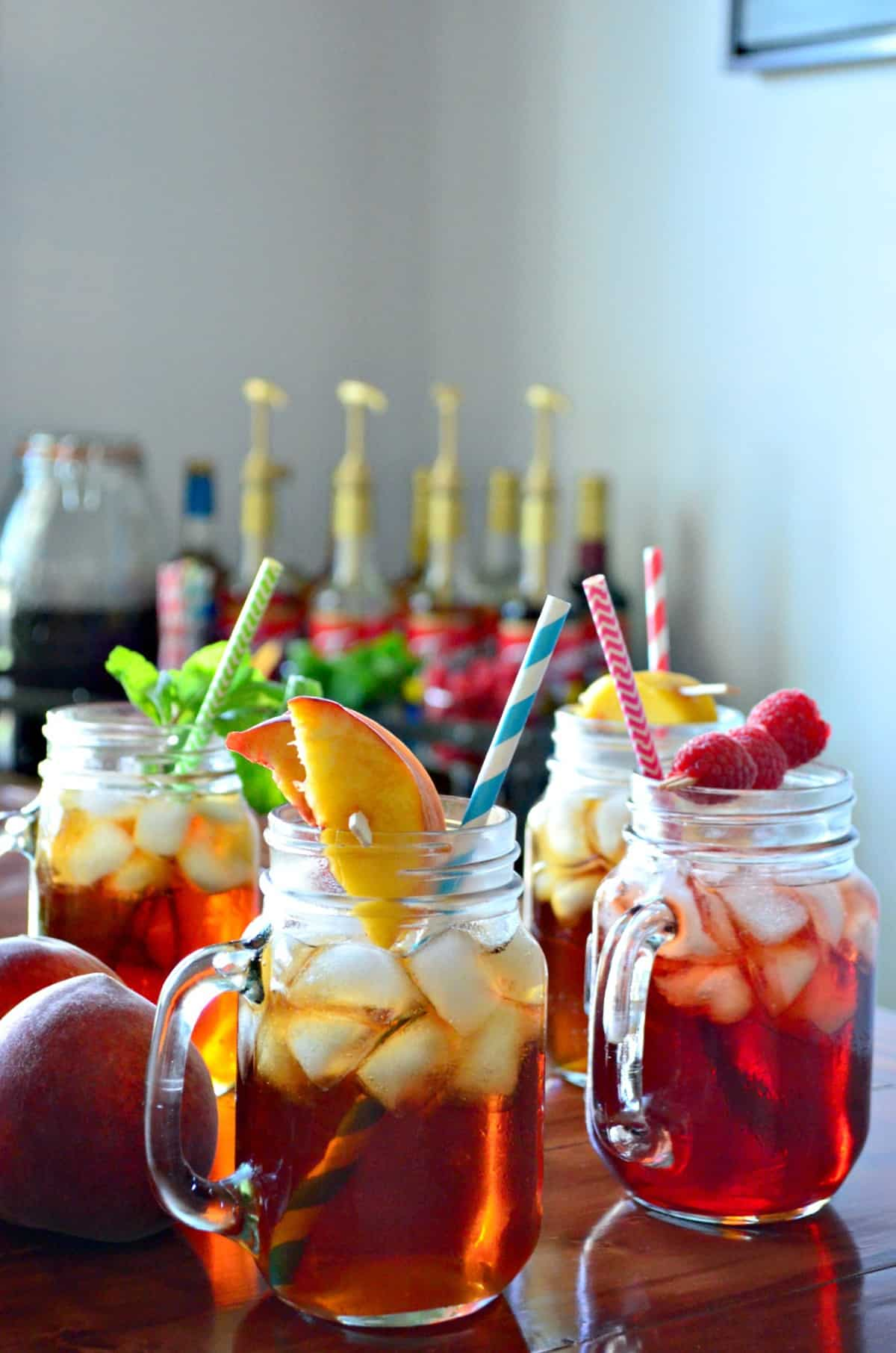 4 glass jars of iced tea, each garnished with a different item like peaches, raspberries, and mint.