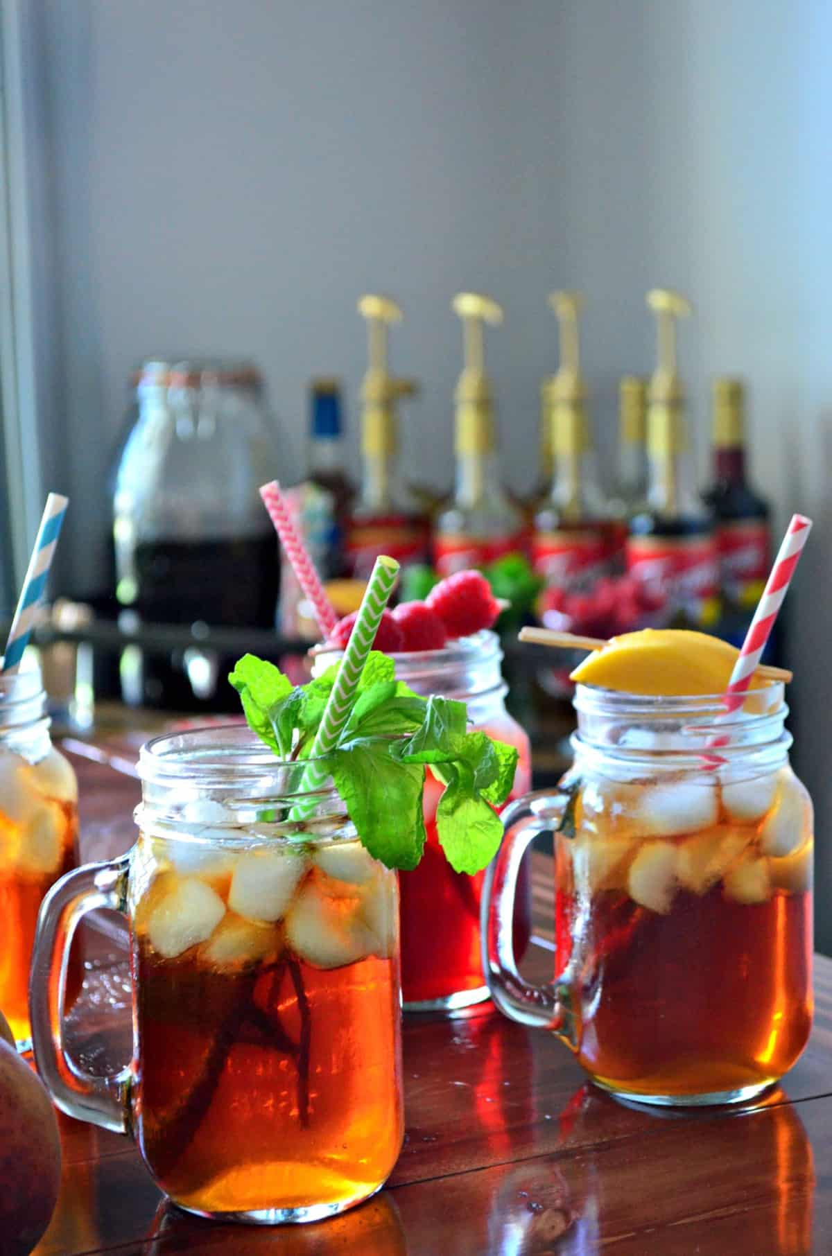 3 glass jars of iced tea, each garnished with a different item like peaches, raspberries, and mint.
