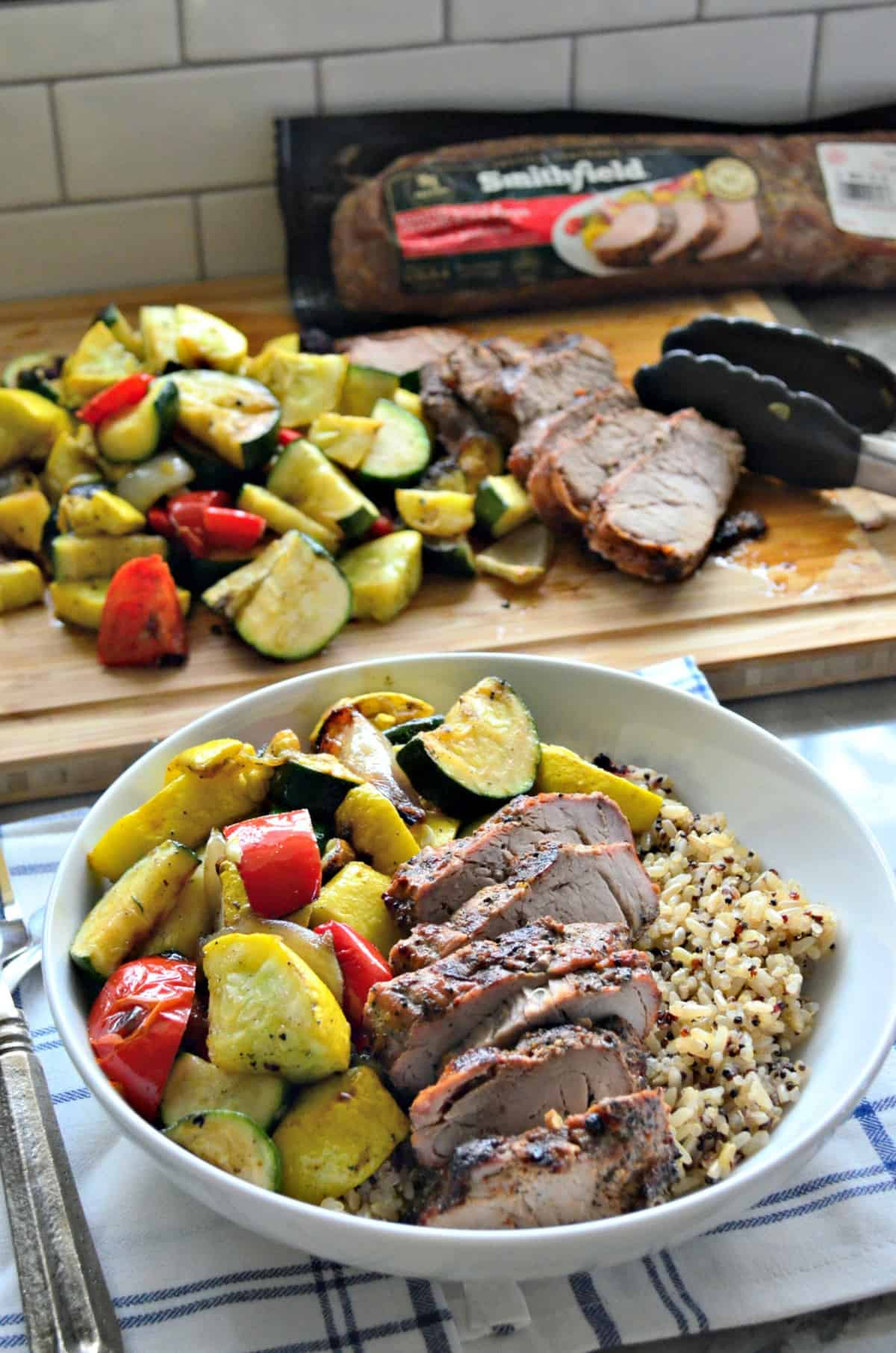 Pork Tenderloin and Brown Rice in a bowl with grilled squash, tomatoes, onions in front of cutting board.