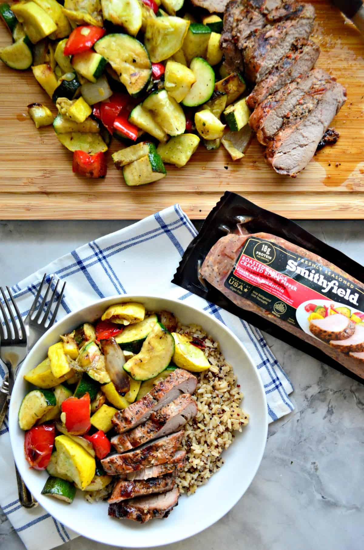 Pork Tenderloin and Brown Rice in a bowl with grilled squash, tomatoes, onions, and with title text.