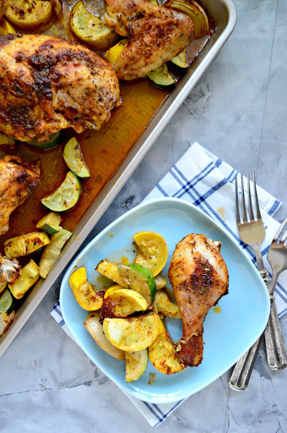 Chicken drumstick with sliced squash and onion on light blue square plate next to sheet pan.