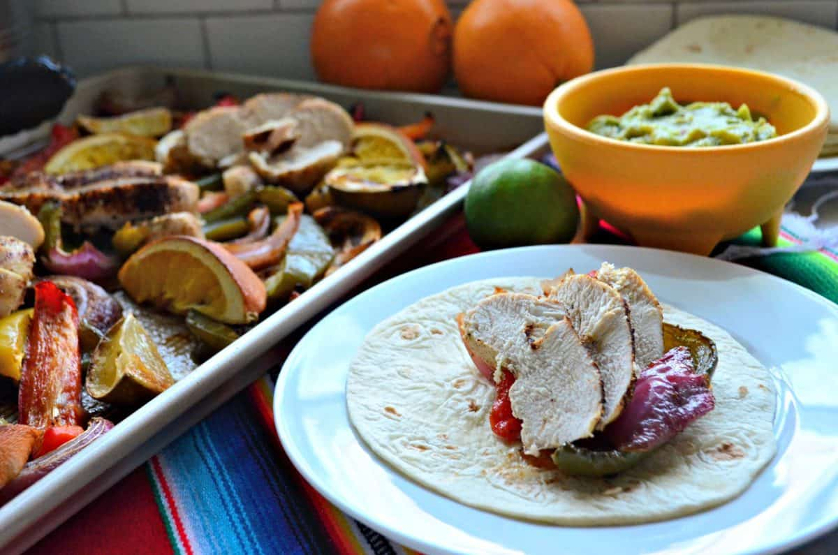 sliced bell peppers, sliced chicken, lemon, and onion on sheet pan next to plated fajita.