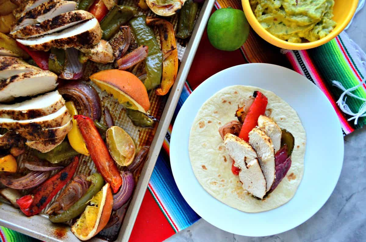 top view of sliced bell peppers, sliced chicken, lemon, and onion on sheet pan next to plated fajita.