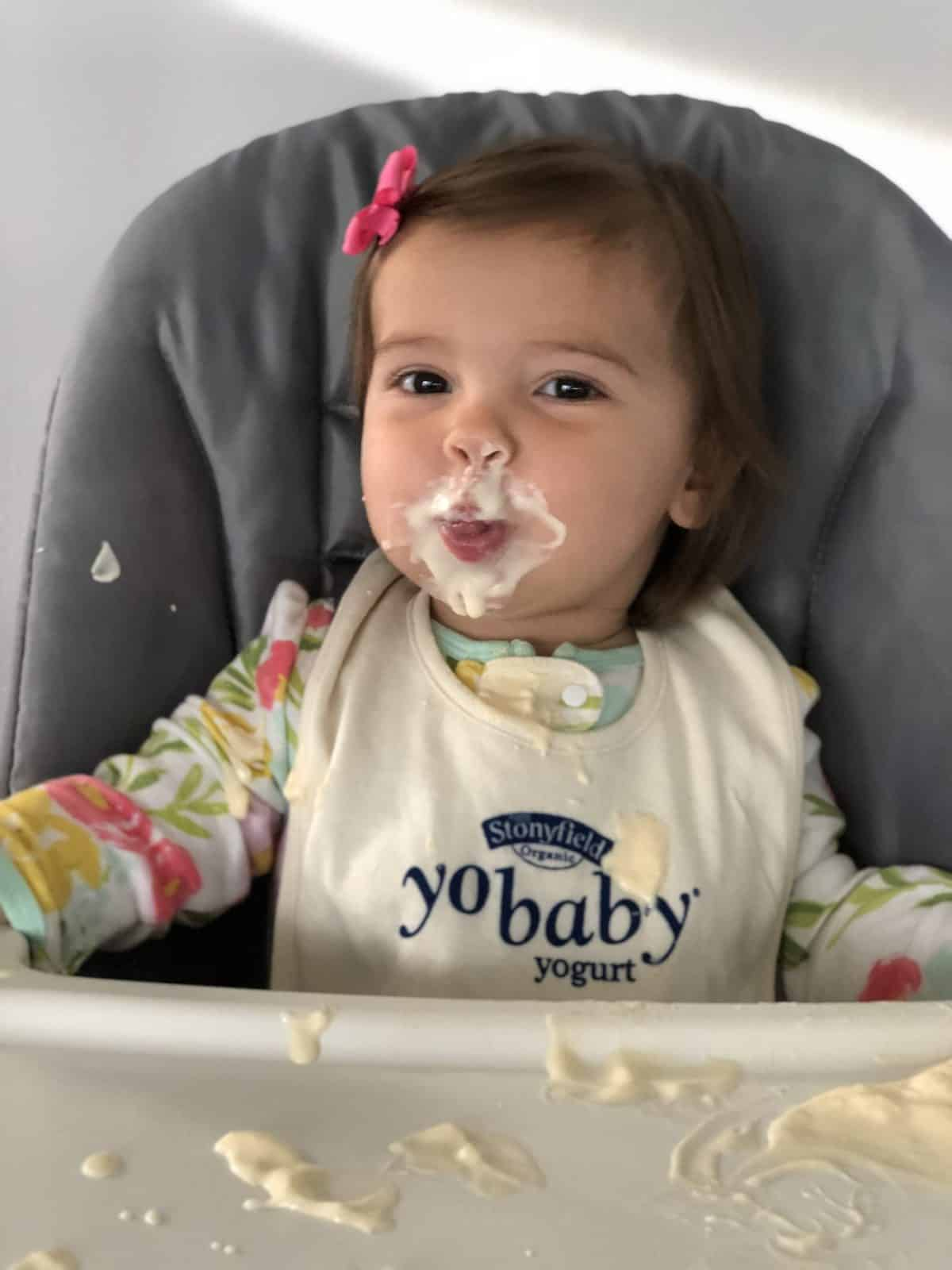 young girl (around 13 months) at high chair smiling with yogurt all over her face with spoon in hand.