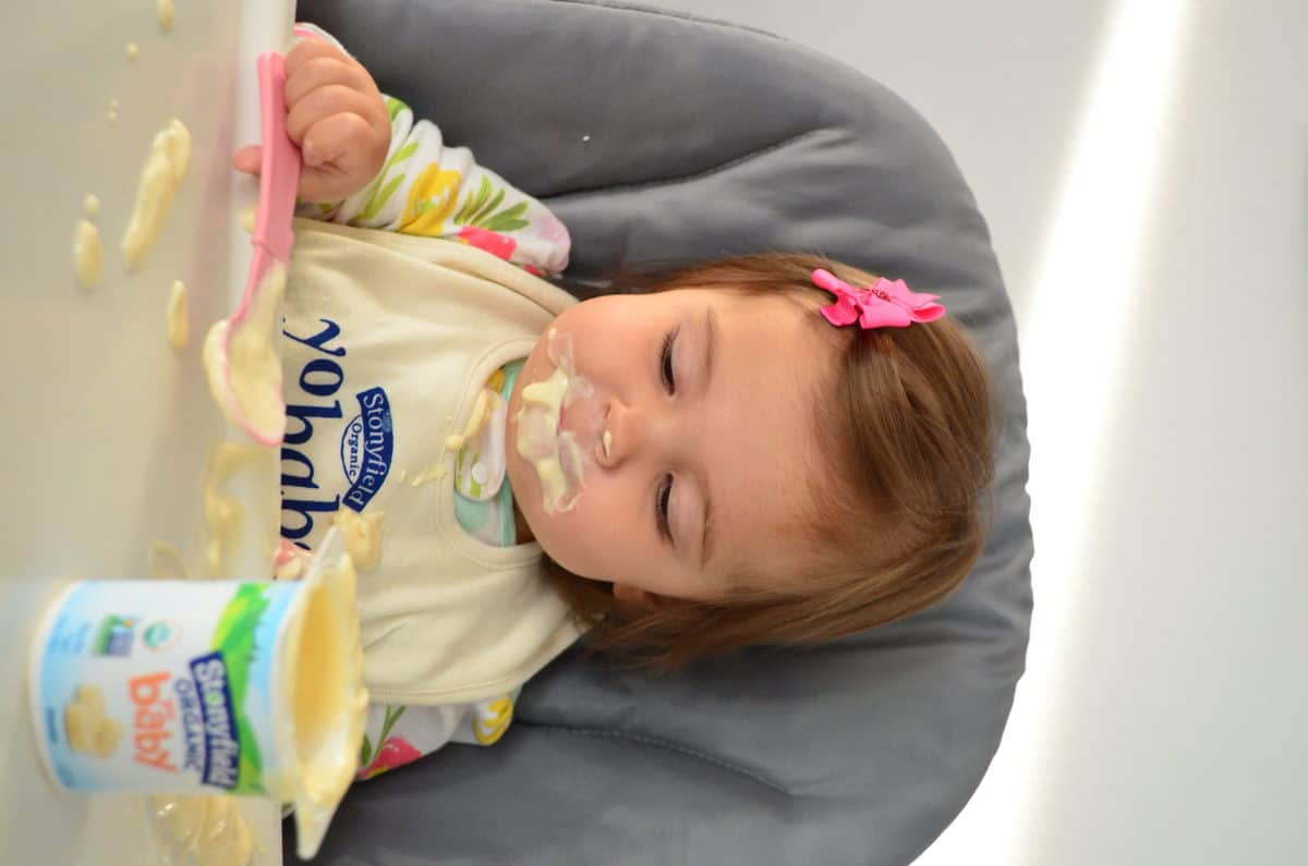 young girl (around 13 months) at high chair grinning with yogurt all over her face with spoon in hand.