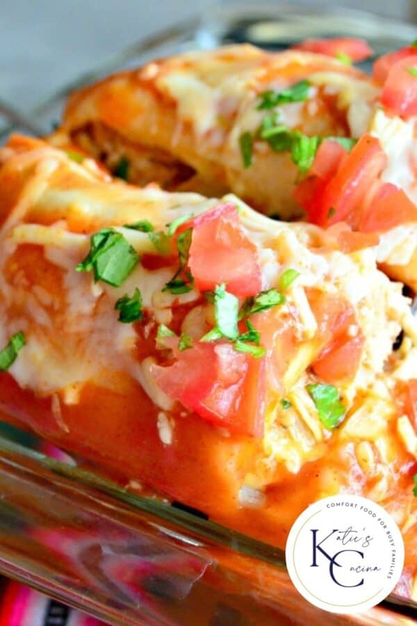Close up of enchiladas in a baking dish with a logo on the right bottom corner.