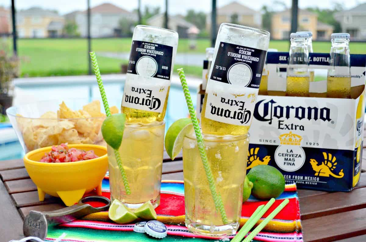 two glasses of light yellow iced liquid with upsidedown corona bottles in them next to chips and salsa.