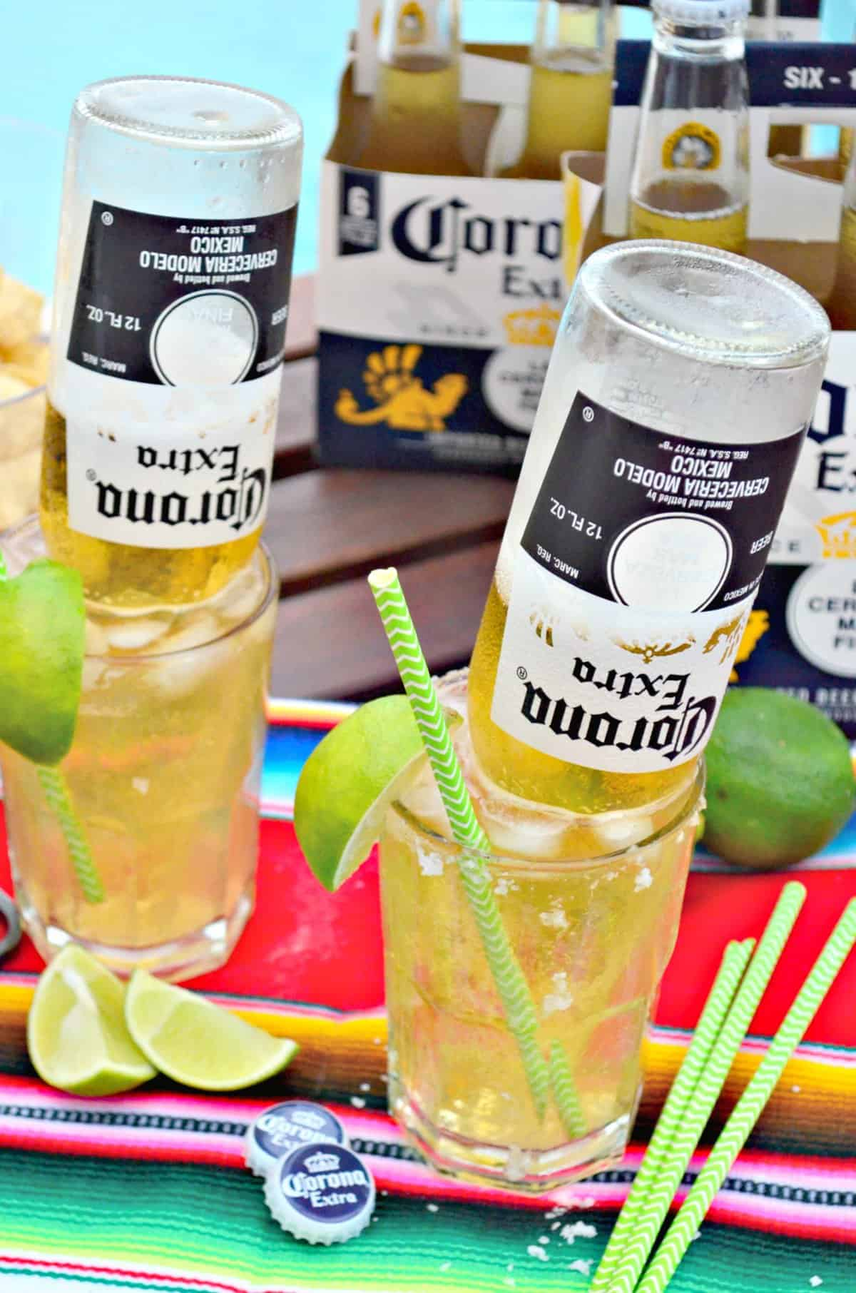 two glasses of light yellow iced liquid with upsidedown corona bottles in them with lime wedges on rim.