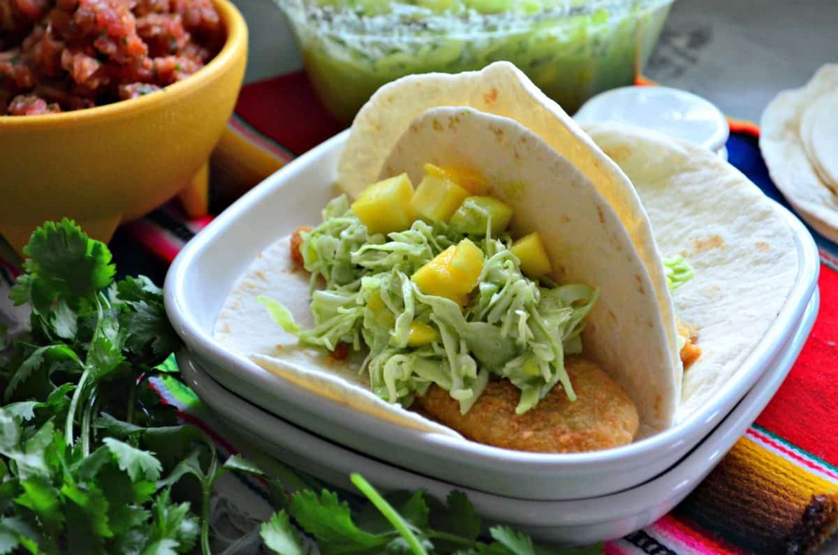 two flour tortilla tacos on a plate with mango coleslaw on it.