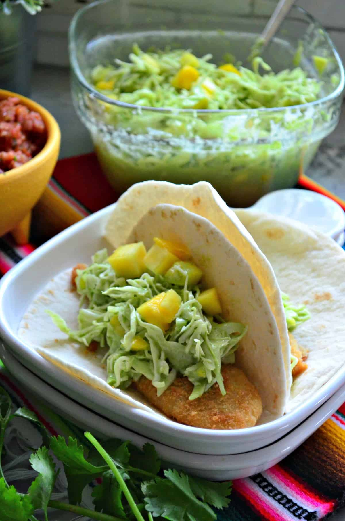 two flour tortilla tacos on plate with mango coleslaw.