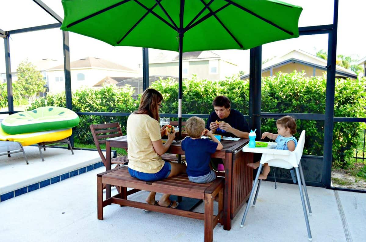 a mom, dad, son, and young daughter enjoying sandwiches at a picnic table with umbrella on backyard pool patio.
