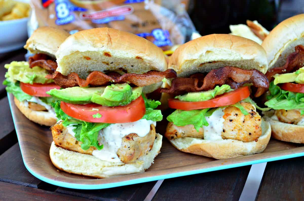 side view of platter of chicken sandwiches on buns with ranch, tomato, lettuce, avocado, and bacon.