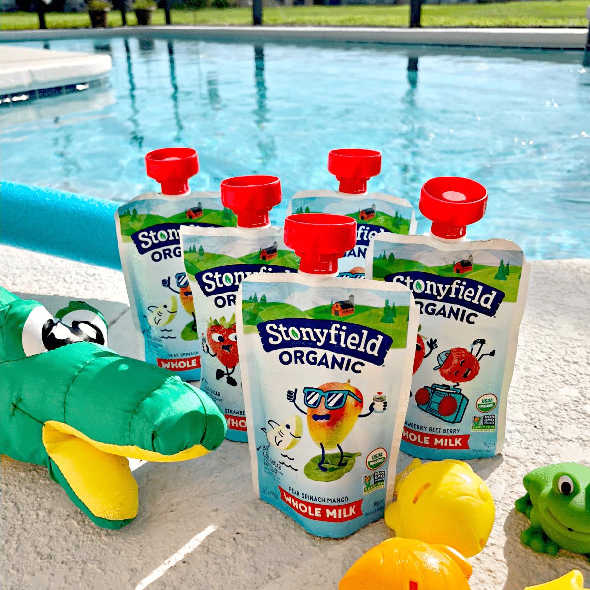 5 flavors of stonyfield organic kid's yogurt sqeeze-packets at poolside.