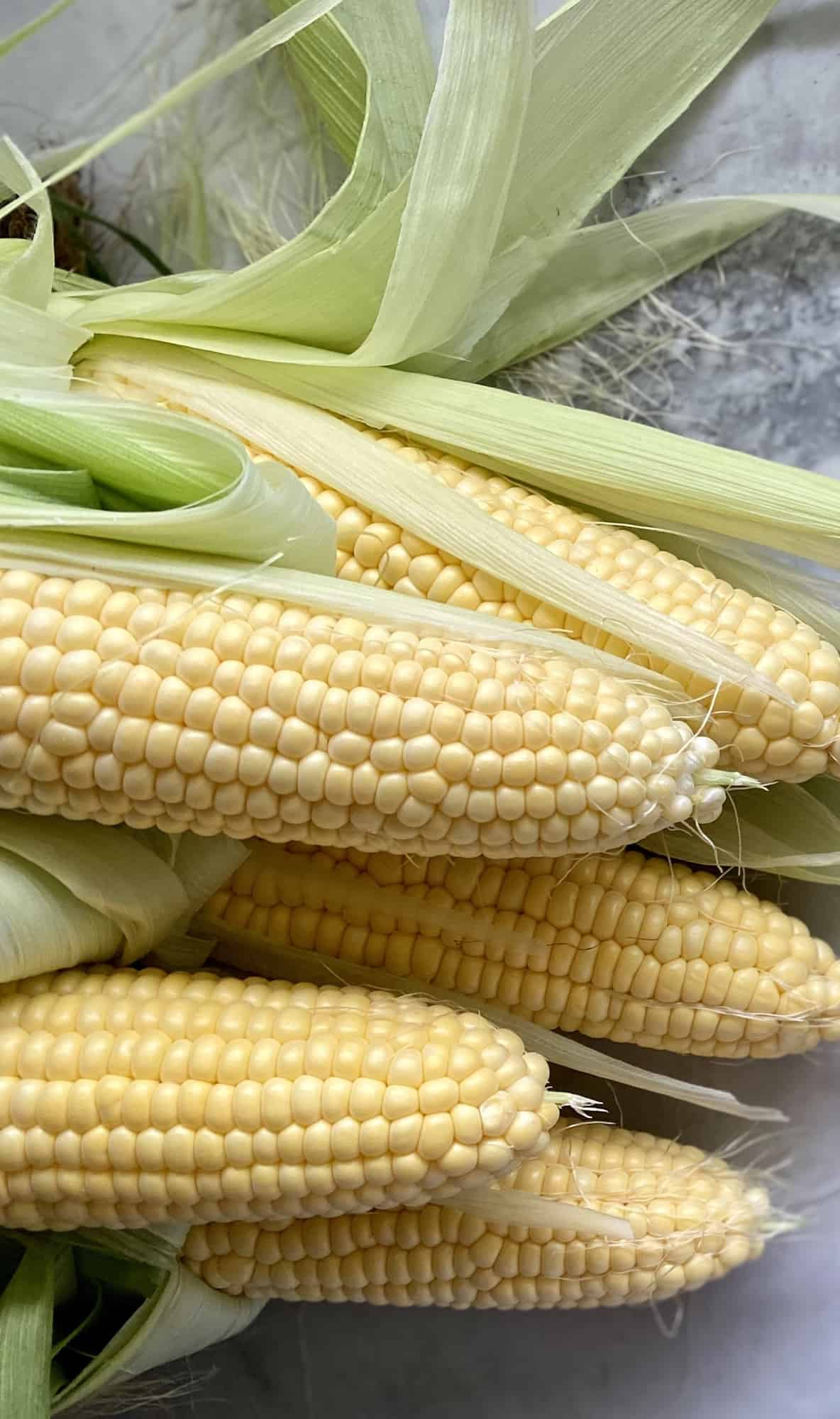 Five ears of corn on the cob on a marble countertop.