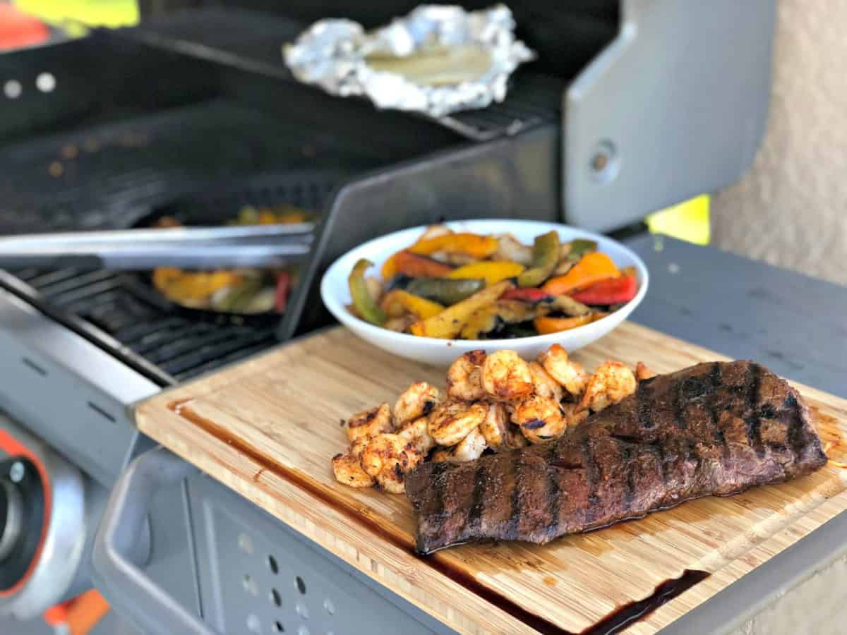 Grilled Skirt Steak next to grilled shrimp and peppers on wooden board next to grill.