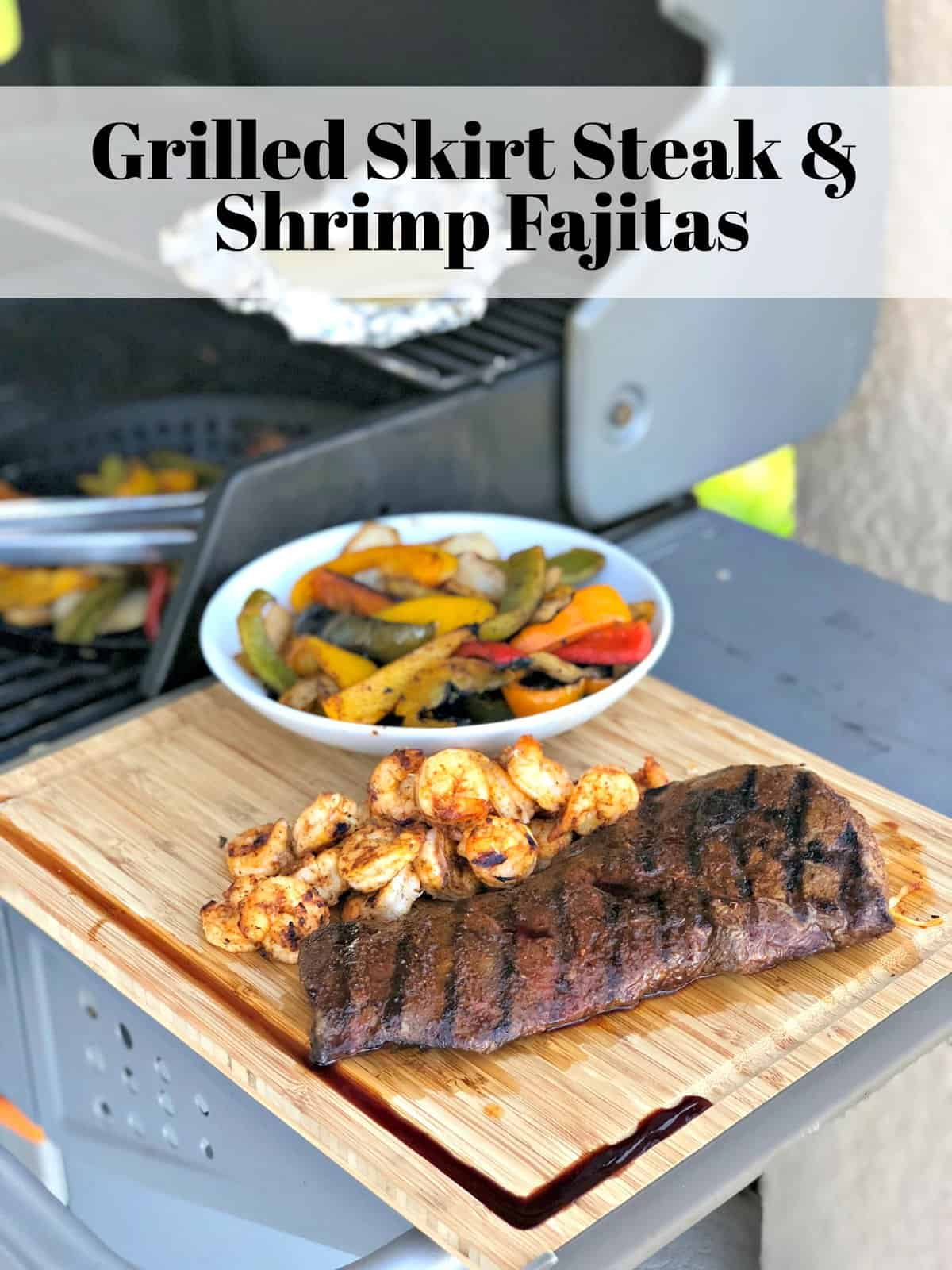 Grilled Skirt Steak next to grilled shrimp and peppers on wooden board with title text next to grill.