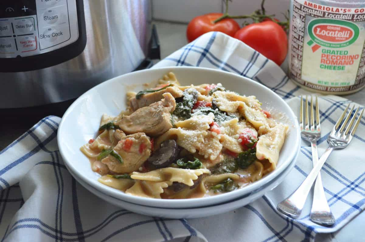 bowl of bowtie pasta with chicken, mushroom, spinach, tomato, and cheese.