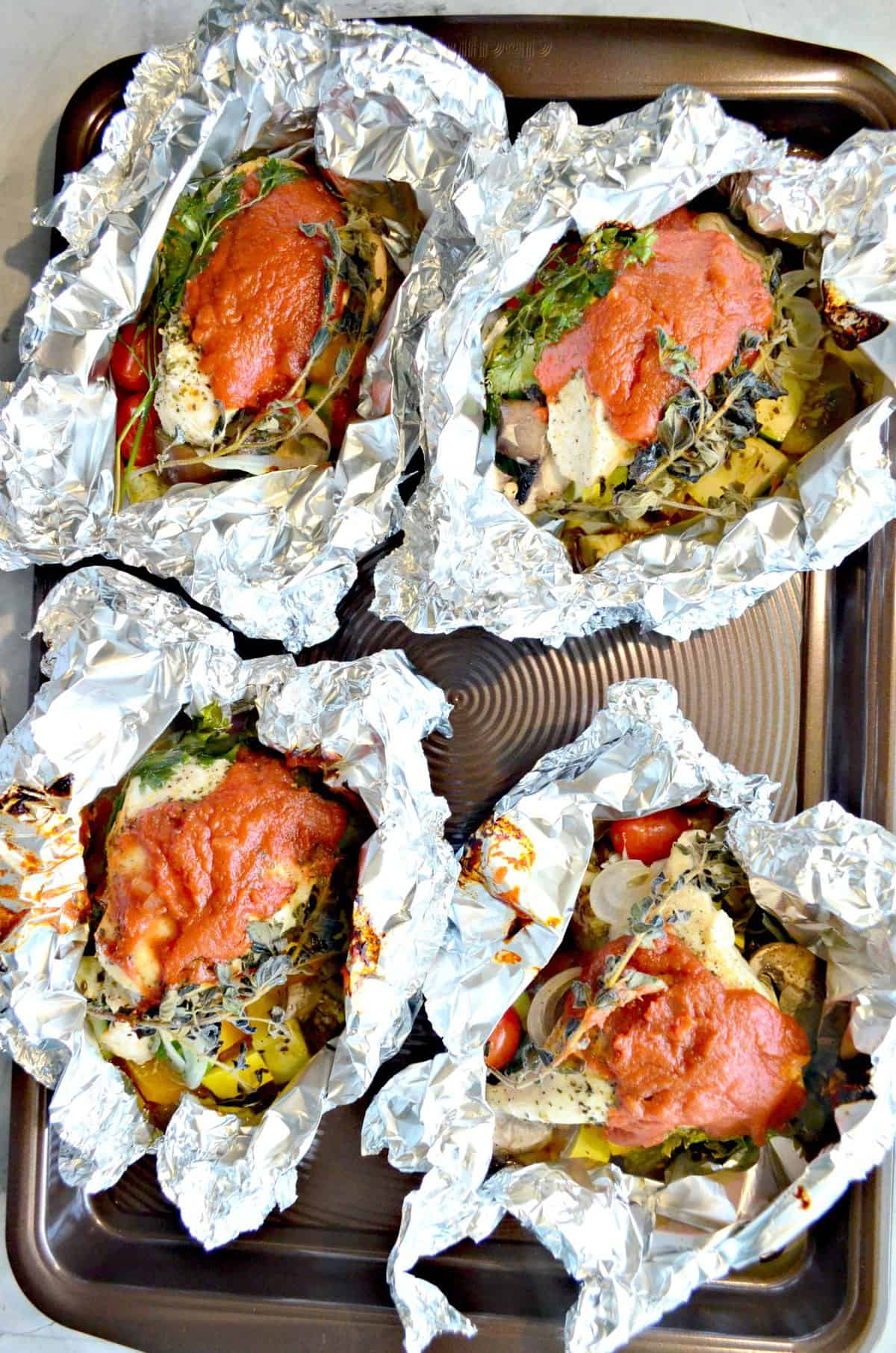 close up of 4 pieces of chicken in an open foil with herbs and red sauce.