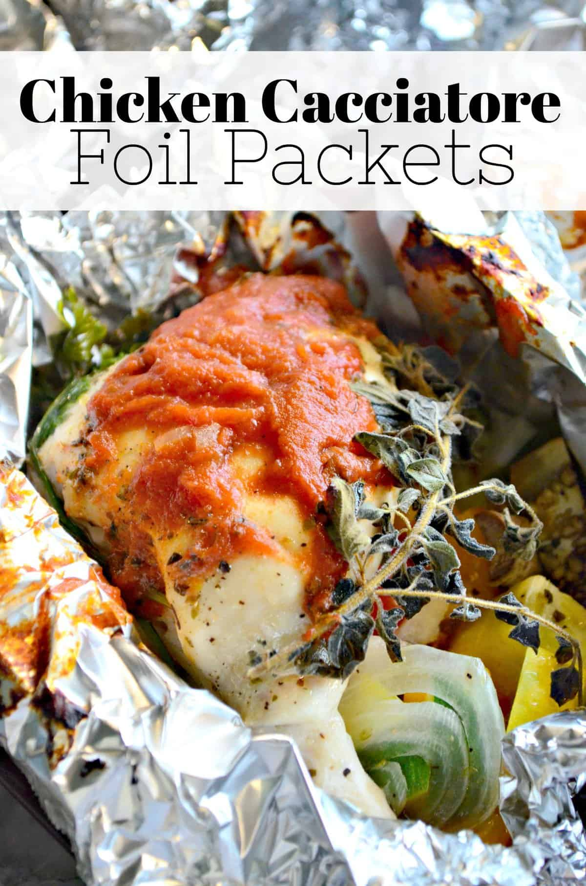 close up of chicken in an open foil with herbs and red sauce.