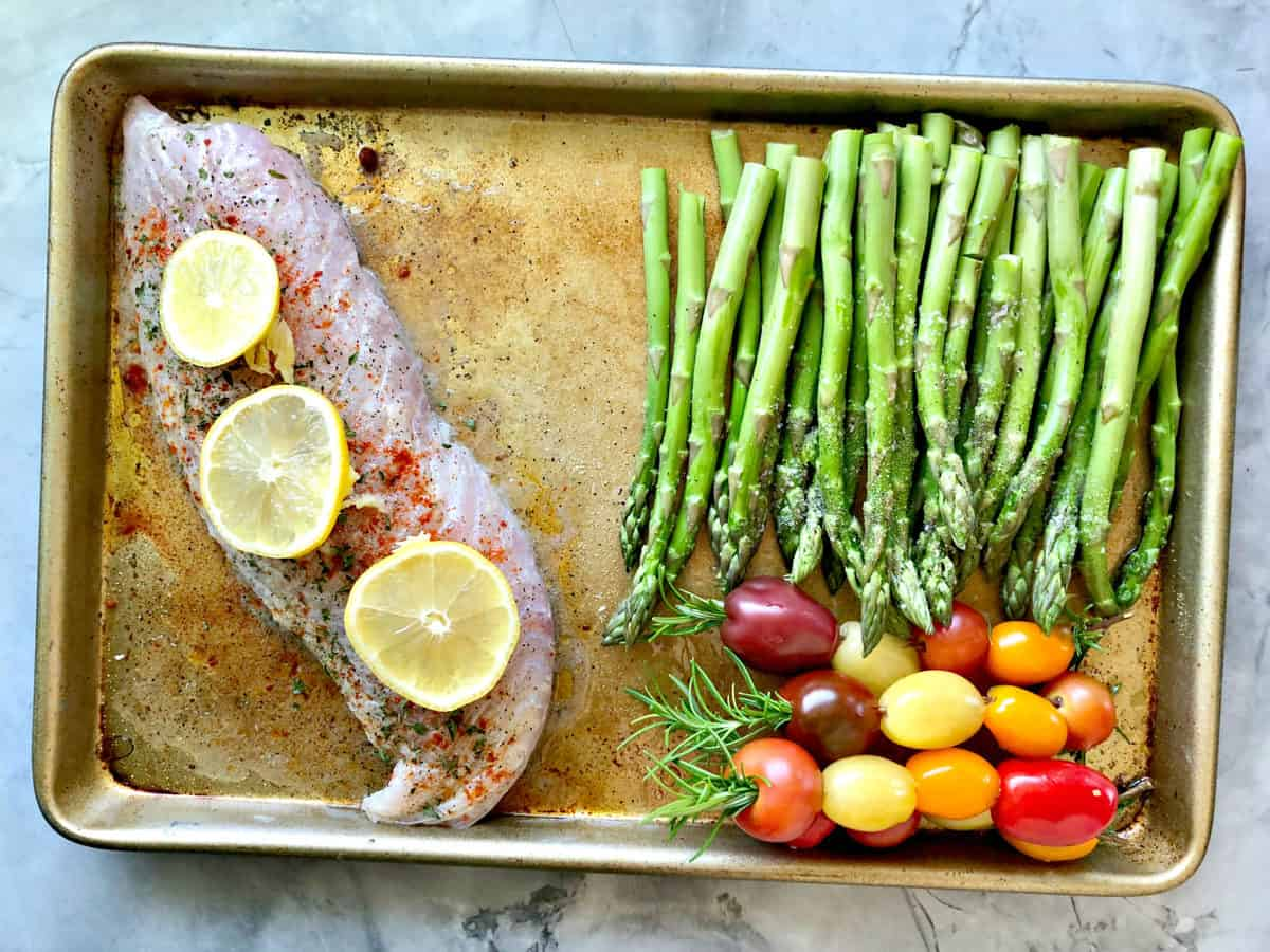 top view baking sheet with uncooked snapper, grape tomatoes, and asparagus.