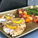 Baking sheet with snapper, blistered tomatoes, and asparagus.