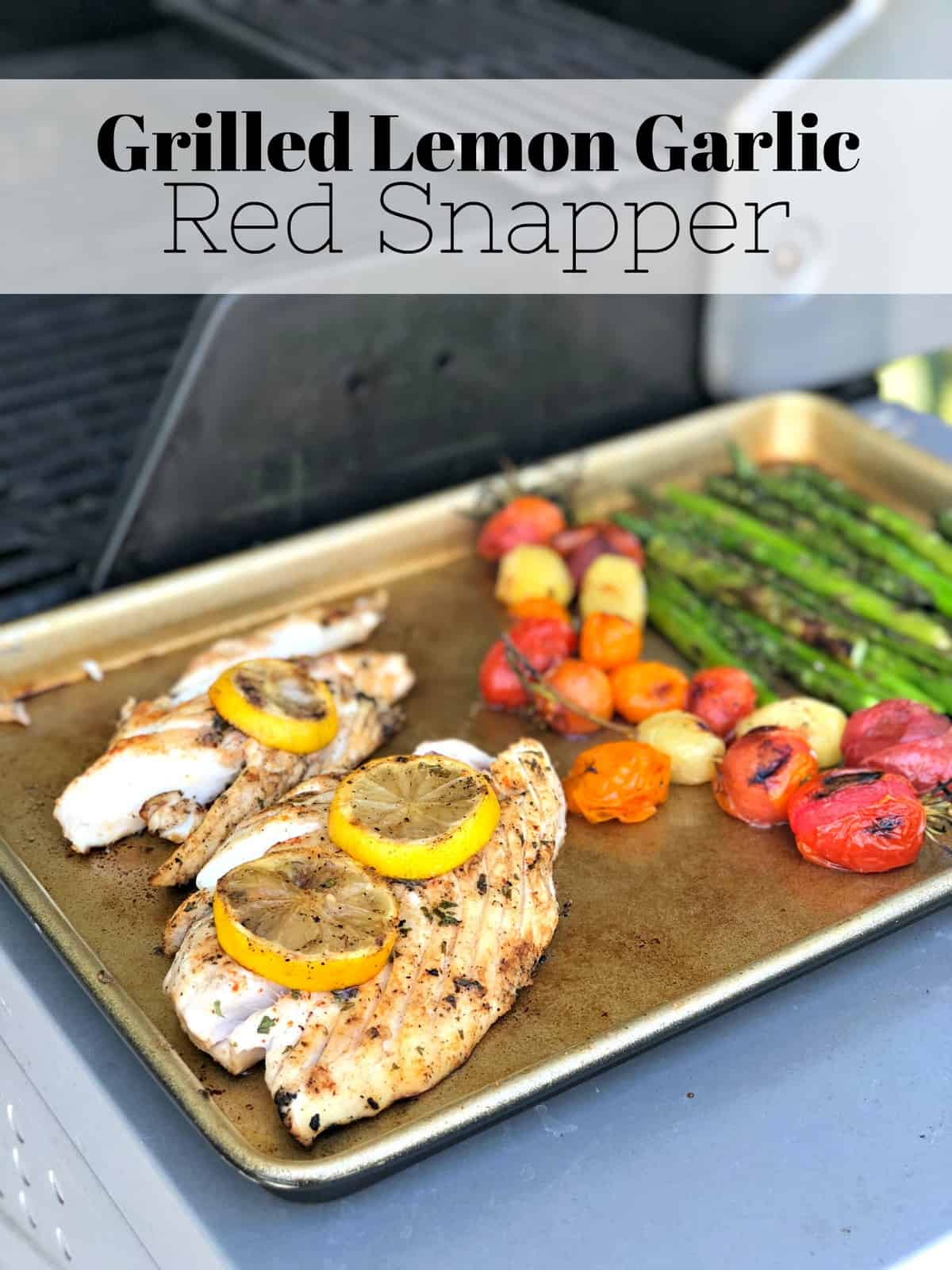 sheet pan with grilled fish topped with lemon wheels, grape tomatoes, and asparagus with title text.