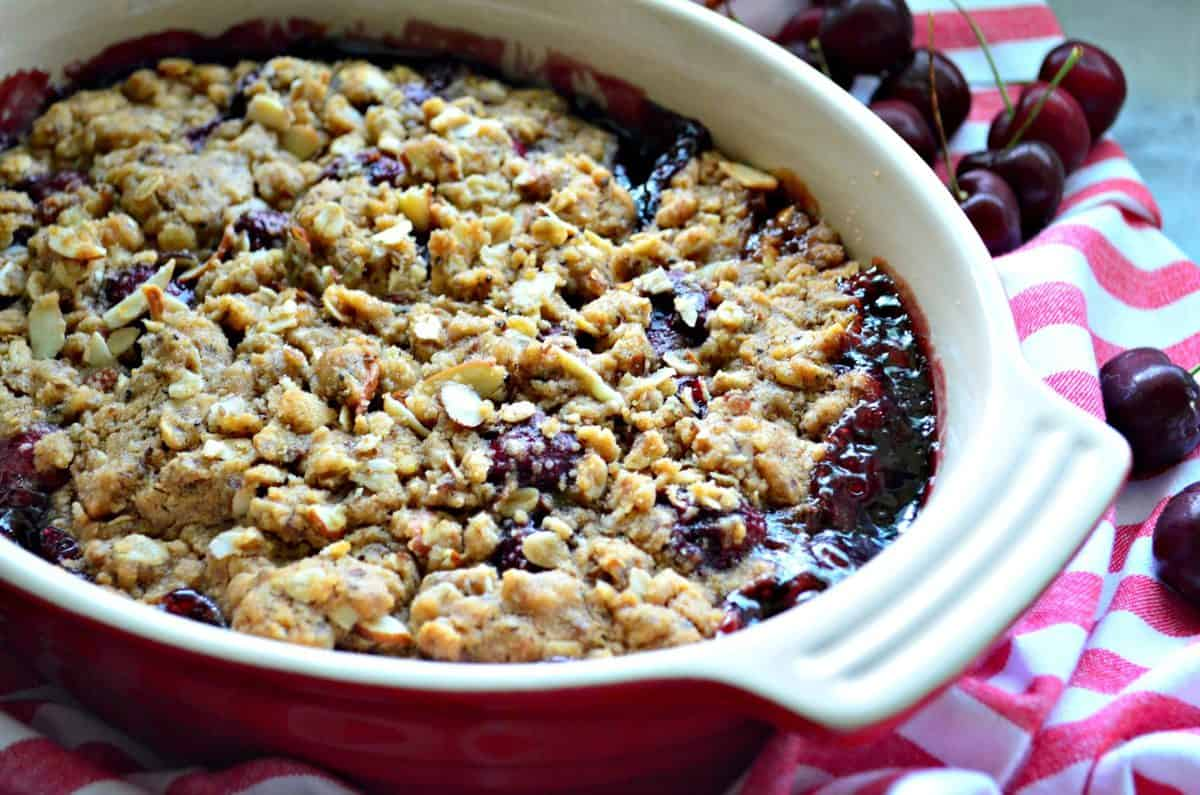 Baked cherries with almonds and crumble topping in a red oval baking dish.