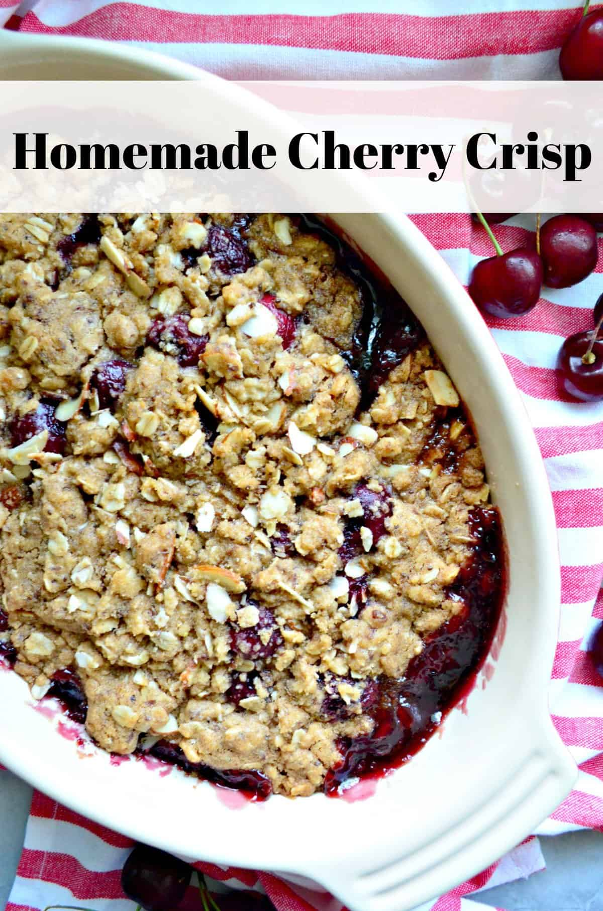 Overhead view of cherry crisp with sliced almonds on a red and white striped cloth with text.