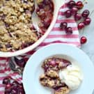dish with cherries and brown crumbles on top next to plate of dessert with ice cream.