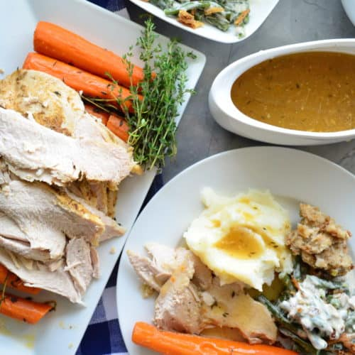 gravy boat, turkey platter, green bean casserole, and plate of turkey, carrots, potatoes, and green beans.
