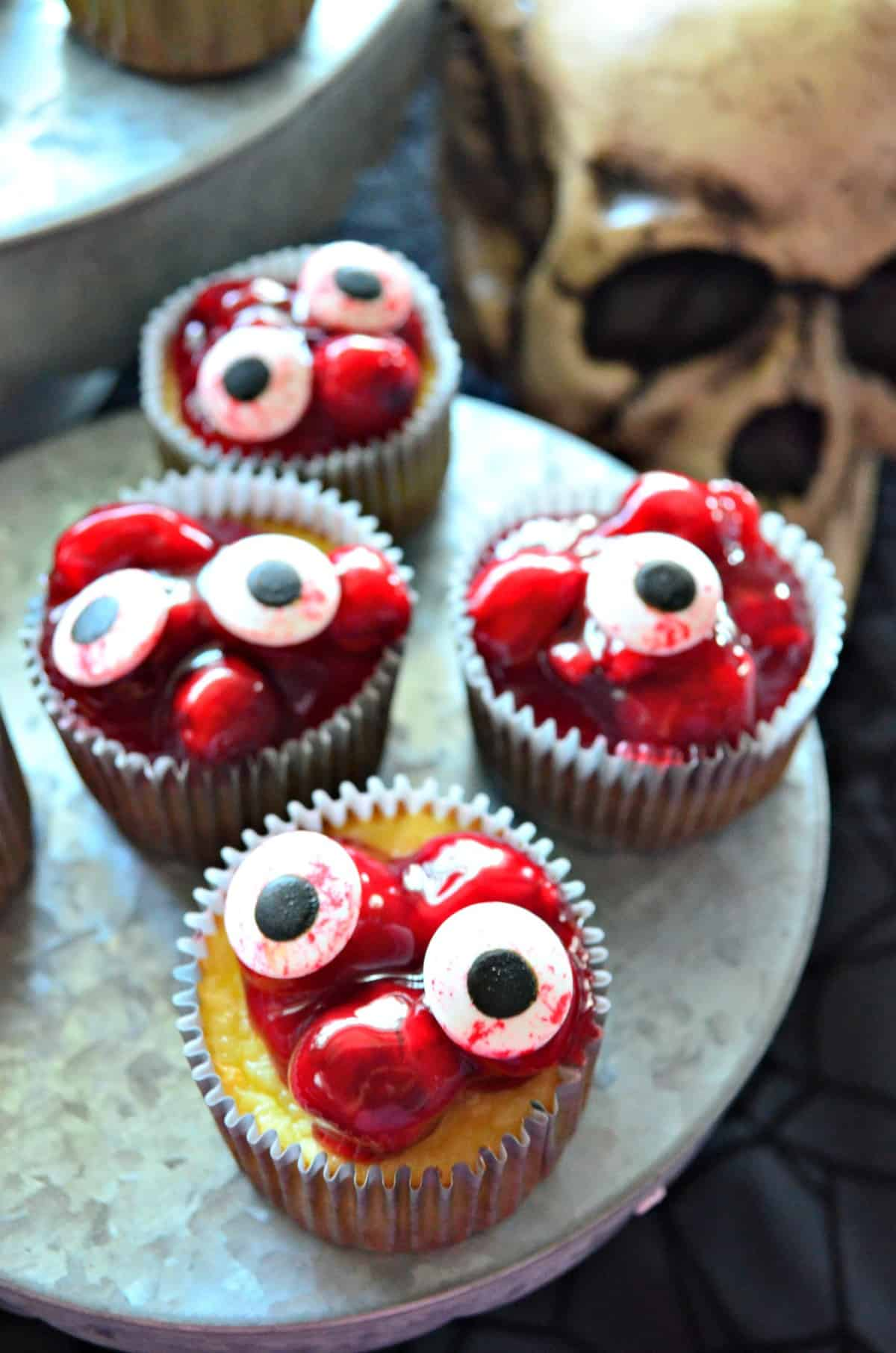 5 cupcakes on cupcake stand topped with red cherries in glaze with candy eyeballs on top.