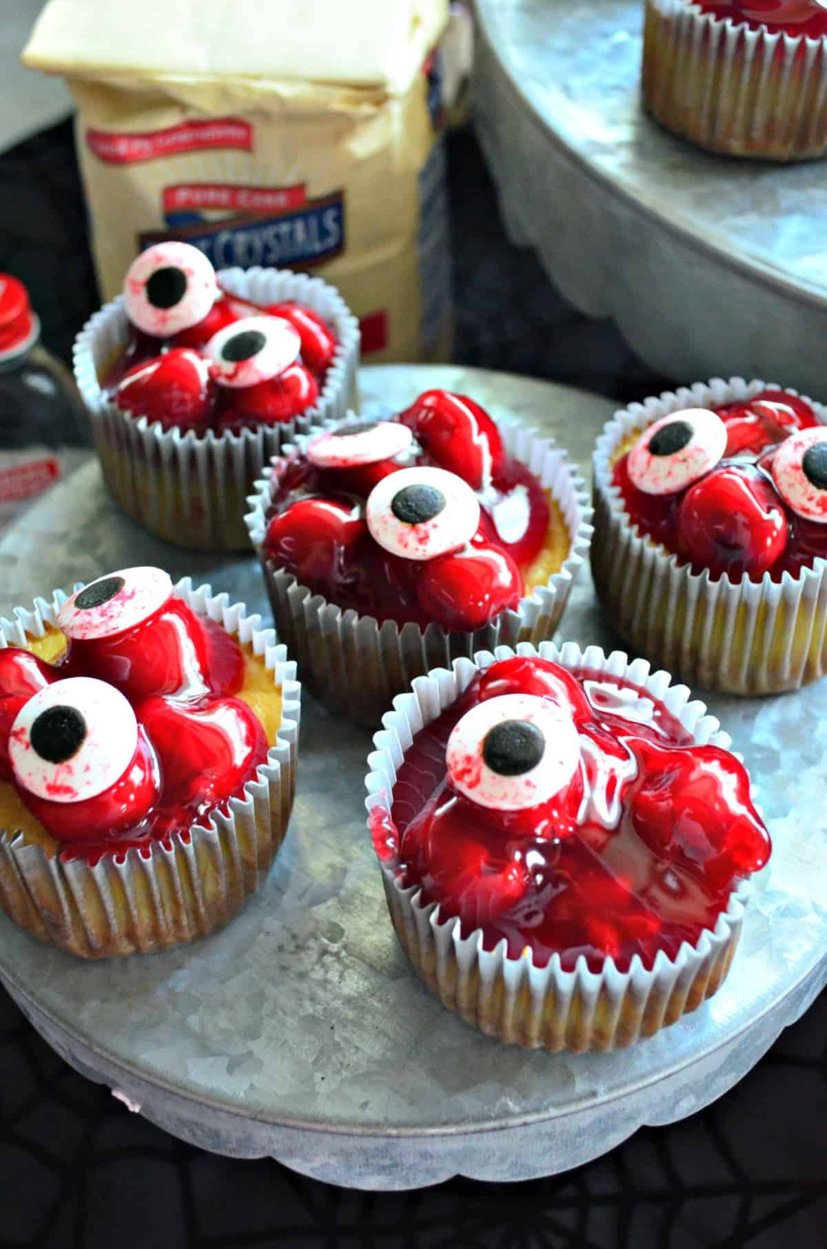 5 cupcakes on cupcake stand topped with red cherries in glaze with candy eyeballs on top and title text.