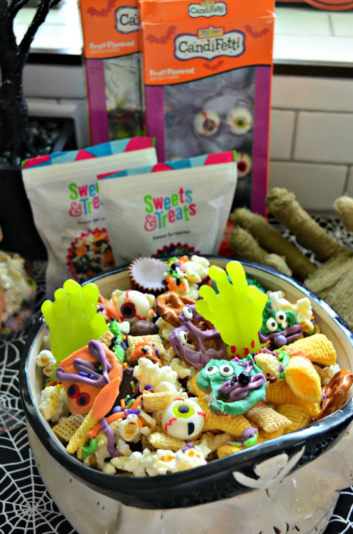 skull bowl of snack mix with colorful chocolate dipped pretzels and candy eyes in front of sweets & treats bags.