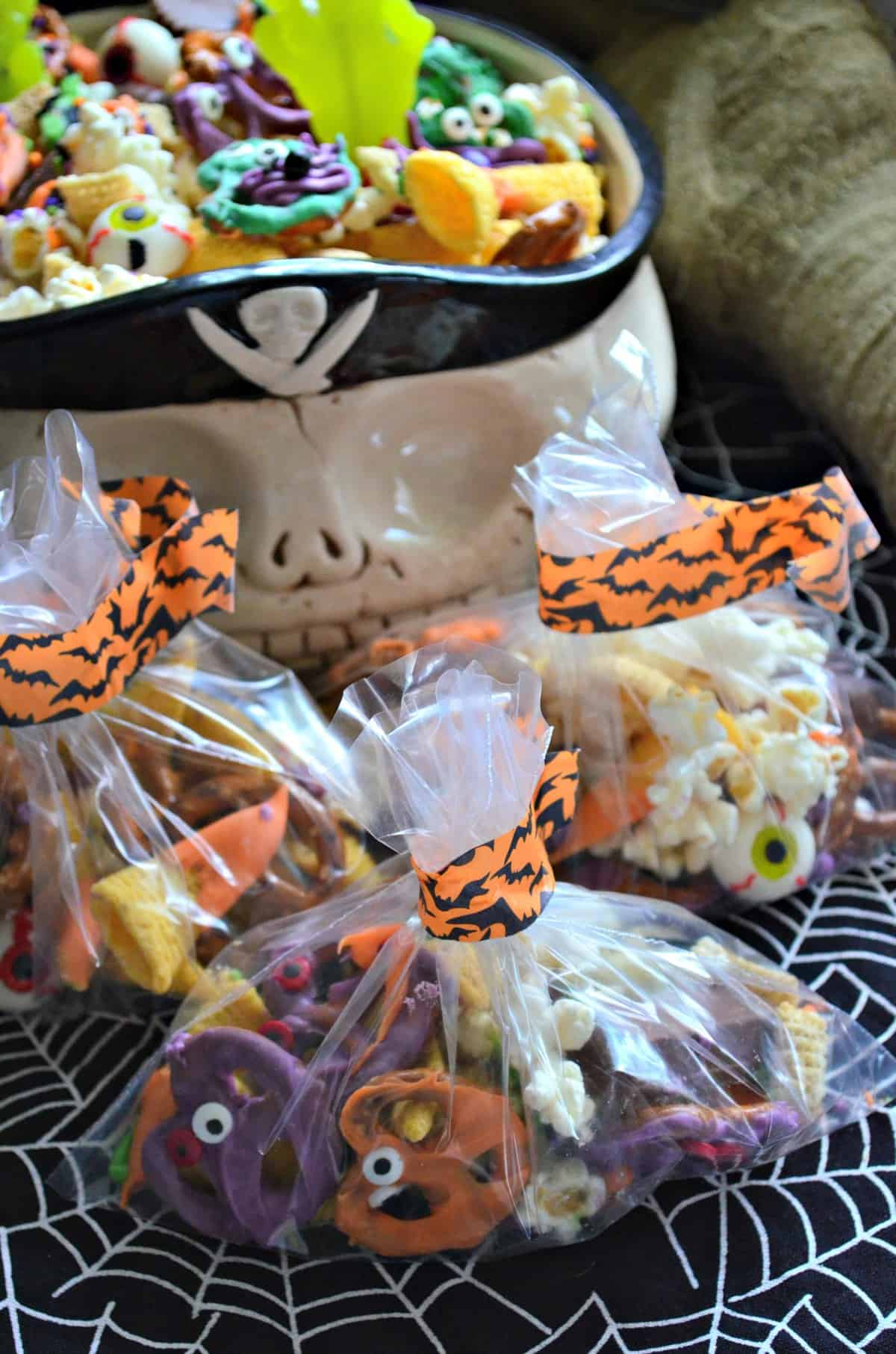 baggies of  snack mix with colorful chocolate dipped pretzels and candy eyes with bowl of snack mix behind.