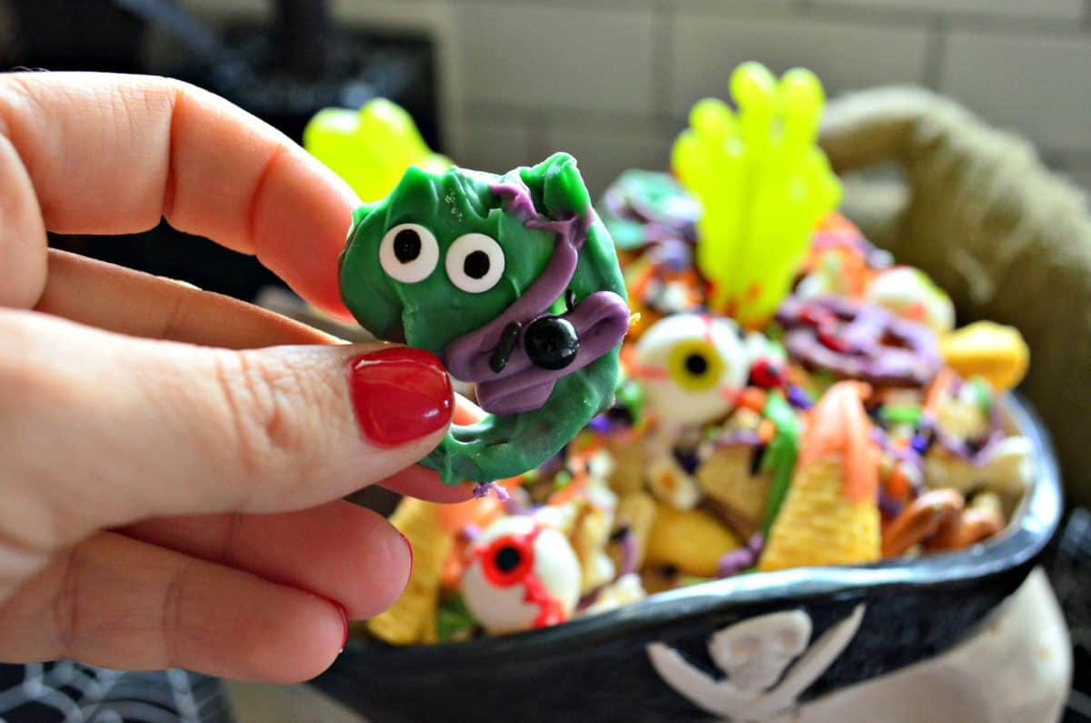 closeup of pretzel covered in green and purple chocolate with candy eyes.