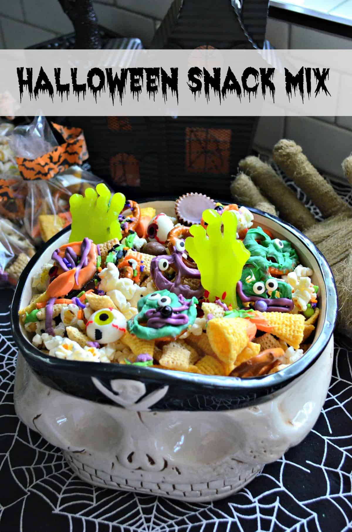 skull bowl of snack mix with colorful chocolate dipped pretzels and candy eyes with title text.